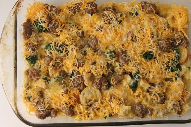 cubed stale french bread, sausage and spinach topped with shredded cheese and an egg and seasoning mixture in a glass baking dish