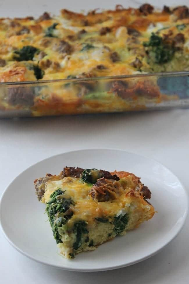 a slice of sausage and spinach strata on a white plate on a white table with the rest of the casserole in a glass dish behind it