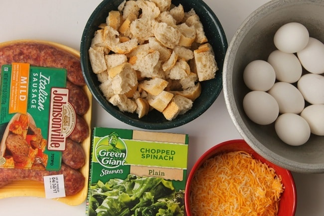eggs, milk, sausage, frozen spinach, stale bread, cheese in packages or bowls on a white background