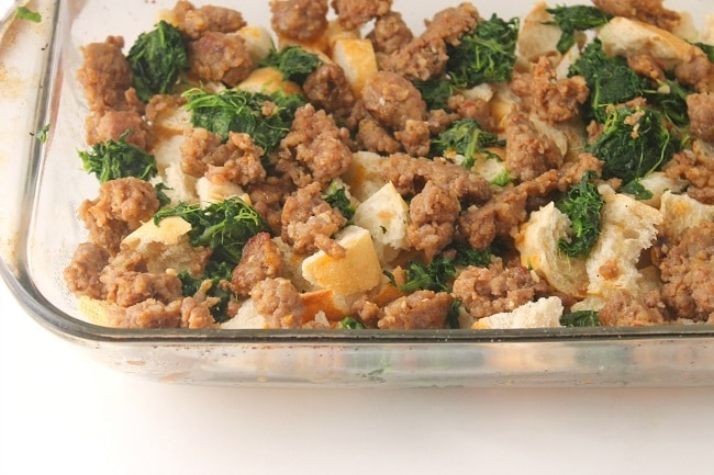 cubed stale french bread, sausage and spinach in a glass baking dish