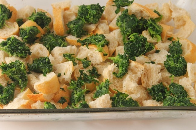 cubed stale french bread and spinach in a glass baking dish