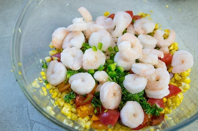 corn, shrimp, tomatoes, red onions, cucumbers, jalapenos, cilantro, parsley, olive oil, lemon juice, salt and pepper in a glass bowl