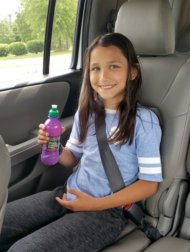 a girl sitting in a car holding a purple fruit shoot drink