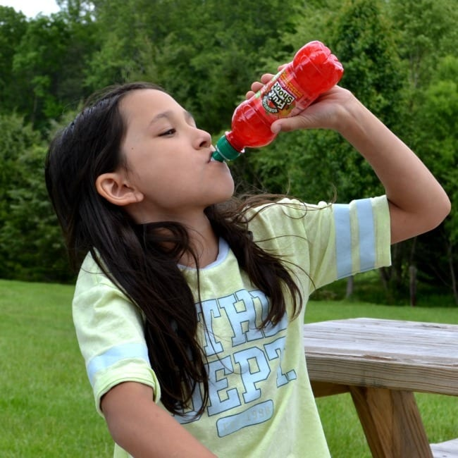 a girl drinking a red fruit shoot while sitting outside