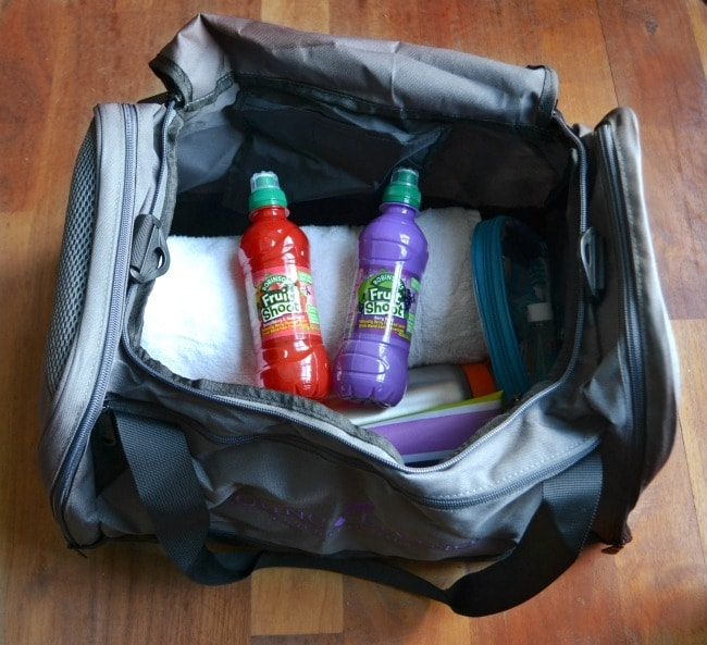 a gym bag with a towel and other things in it, and two fruit shoot drinks