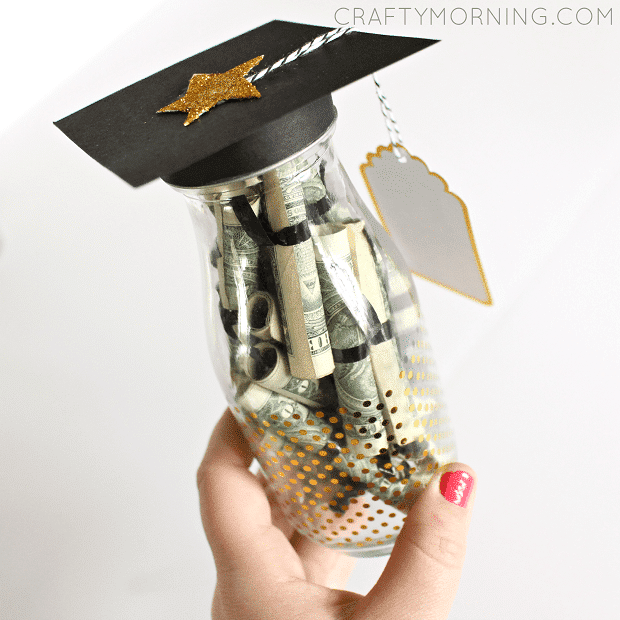 best high school graduation gift ideas - money rolled in a glass jar topped with a graduation cap
