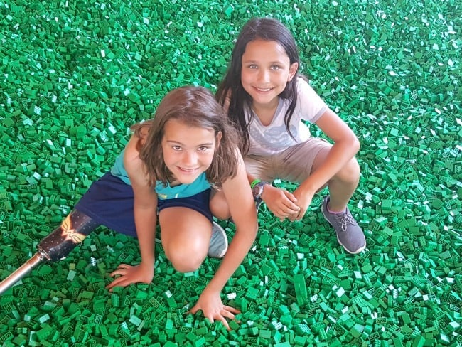 two girls in a pit full of green legos