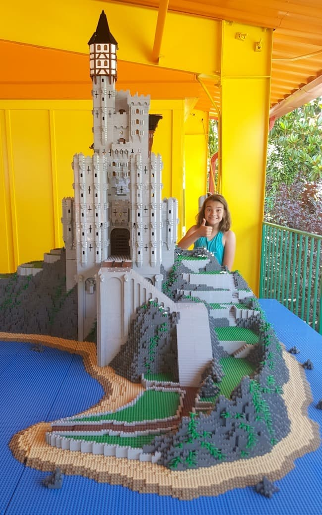 a girl giving a thumbs up behind a huge lego castle creation