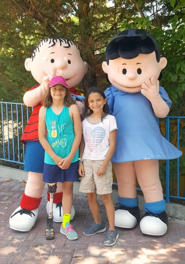 two girls standing with Linus and Lucy characters
