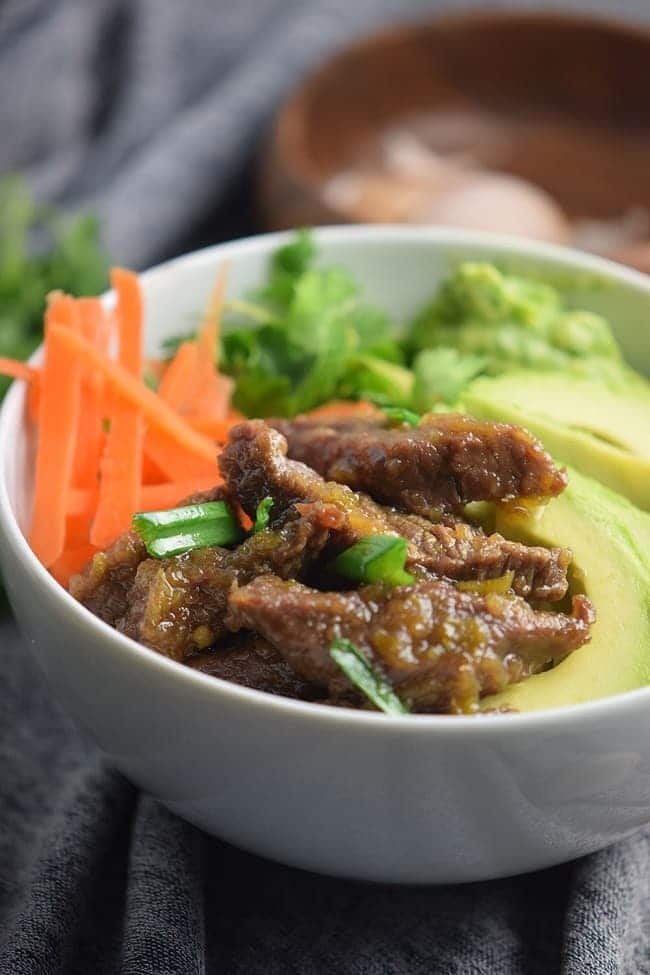 Mongolian beef bowl in a white bowl next to garlic in a wood bowl on a gray cloth