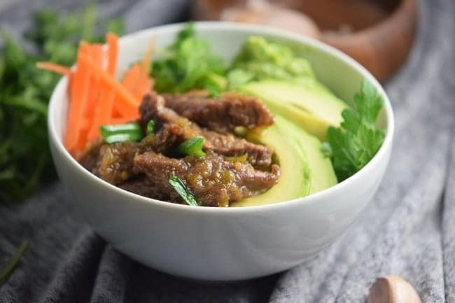 mongolian beef bowl in a white bowl on a gray cloth