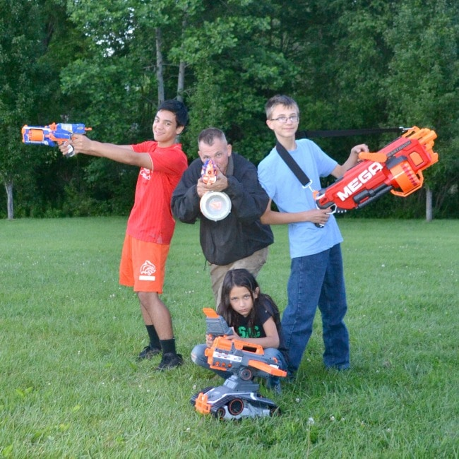a dad, two boys and a girl holding nerf guns on the grass with trees in the background