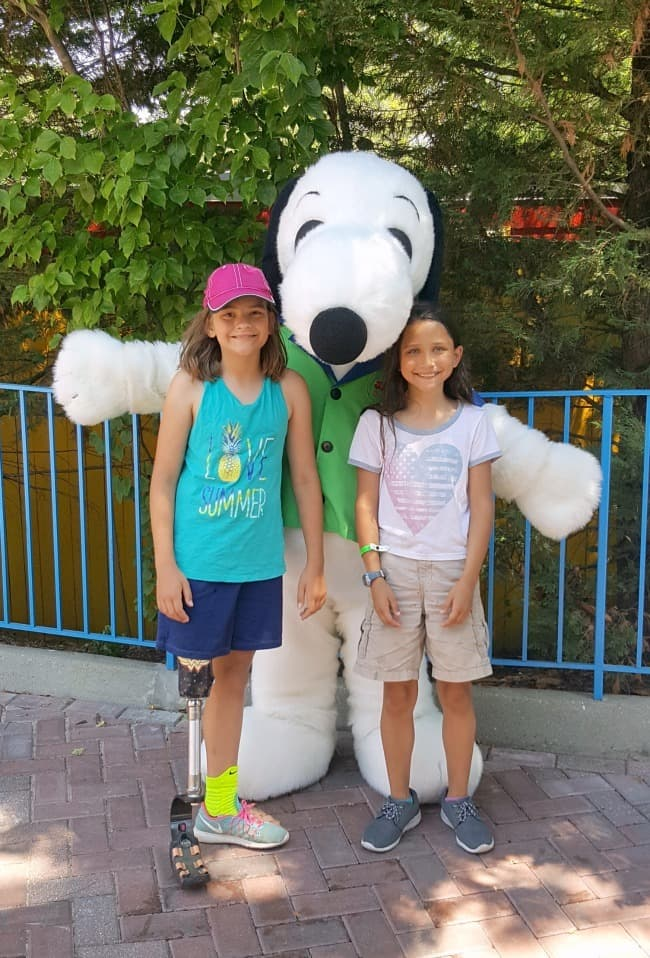 two girls standing with a Snoopy character