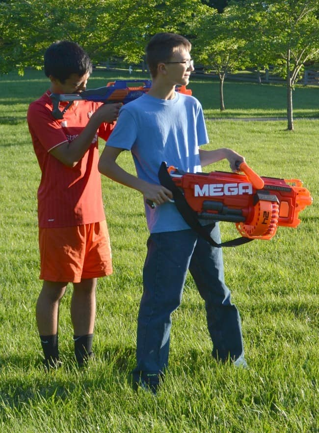 two brothers holding their nerf guns outside