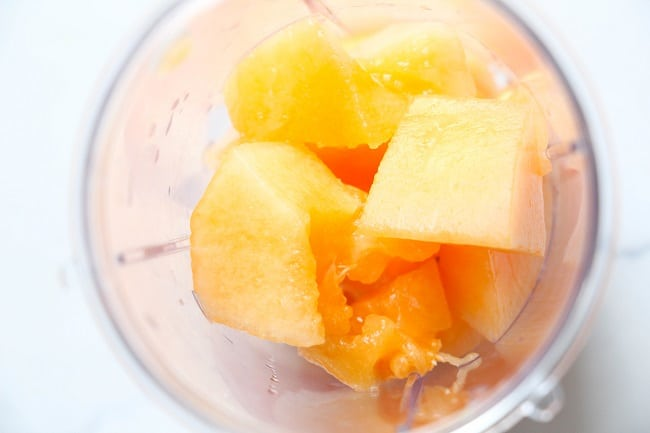 overhead view of cut up cantaloupe in a blending cup