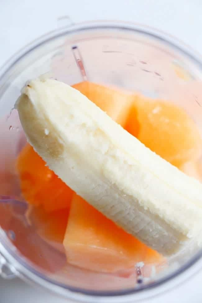 overhead view of cut up cantaloupe and half a banana in a blending cup