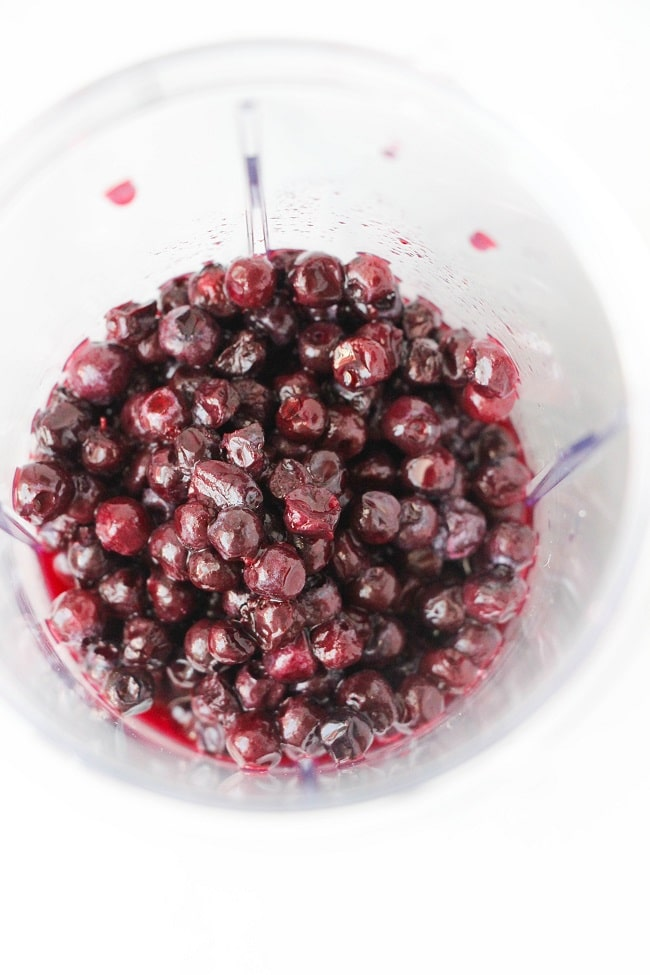 overhead view of blueberries in a blender with a white background