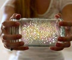 a person holding a jar with glowing things inside called fairies in a jar