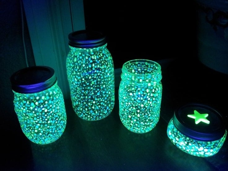 four mason jars in the dark that have glowing circles on them