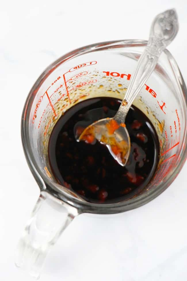 overhead view of soy sauce, ketchup, honey and garlic in a glass liquid measuring cup with a spoon in it on a white background