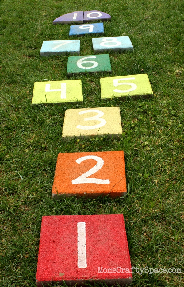 painted squares numbered one to 10 set up to play hopscotch on the grass