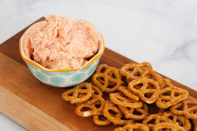 smoked salmon dip in a bowl next to pretzels on a wood board on a white counter