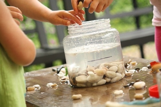 kids outside putting rocks in a jar filled with water