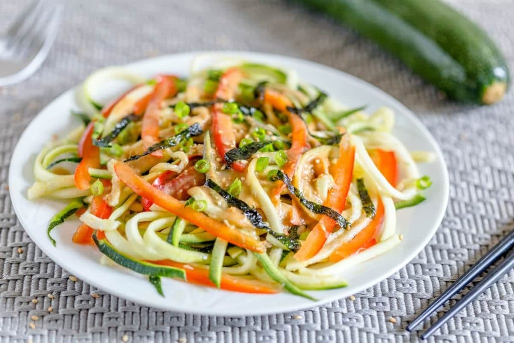Japanese zucchini noodle salad with miso dressing on a white plate next to chopsticks on a gray mat with a zucchini in the background