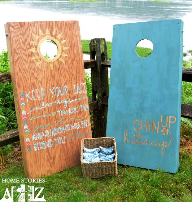 two cornhole boards leaning on a fence on the grass next to a wicker basket with bean bags in it