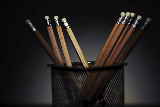 a pencil cup with pencils in it on a dark background