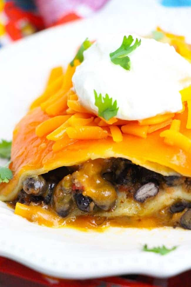 a close up of taco lasagna topped with sour cream and parsley on a white plate on a colorful flowered cloth