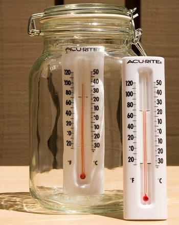 a glass jar with a thermometer in it and next to it on the table