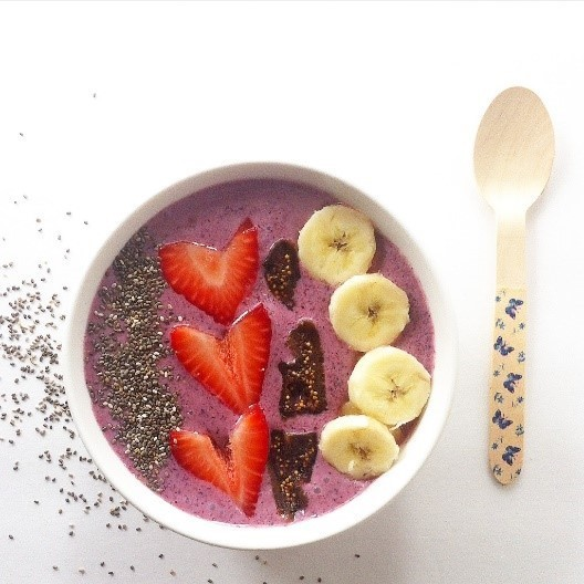 berry chia smoothie bowl next to a spoon on a white background with chia seeds on it