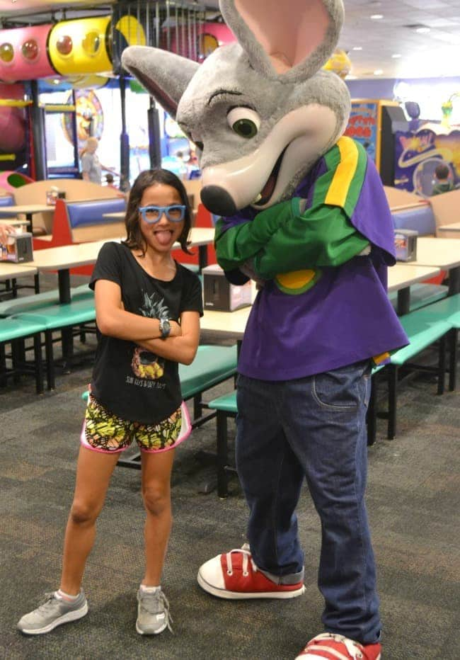 a girl standing with Chuck E. Cheese