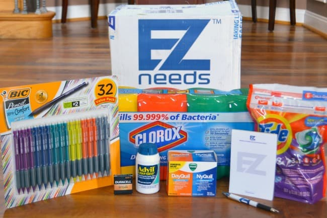 pens, cleaning supplies, medicine with an EZ needs box behind it all