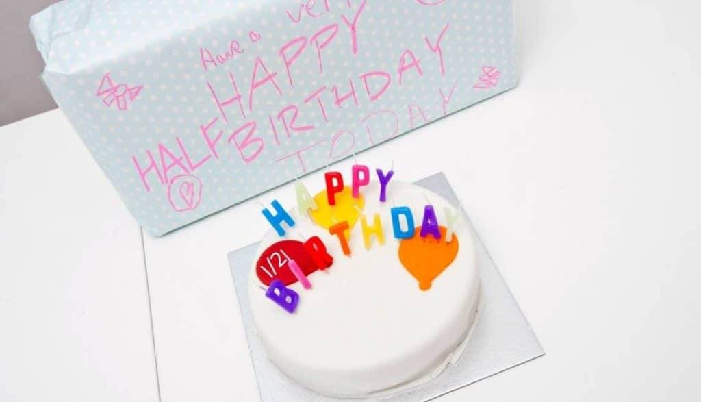 a birthday cake with white frosting and candles that spell Happy Birthday with a gift in the background with text reading Have a Very Happy Half Birthday Today