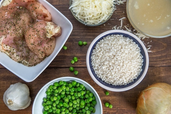 chicken, cheese, broth, risotto, and peas in bowls next to an onion and garlic on a brown table
