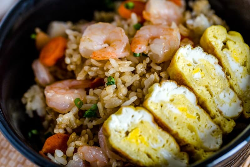 close up view of Japanese fried rice with shrimp in a black bowl on a bamboo mat