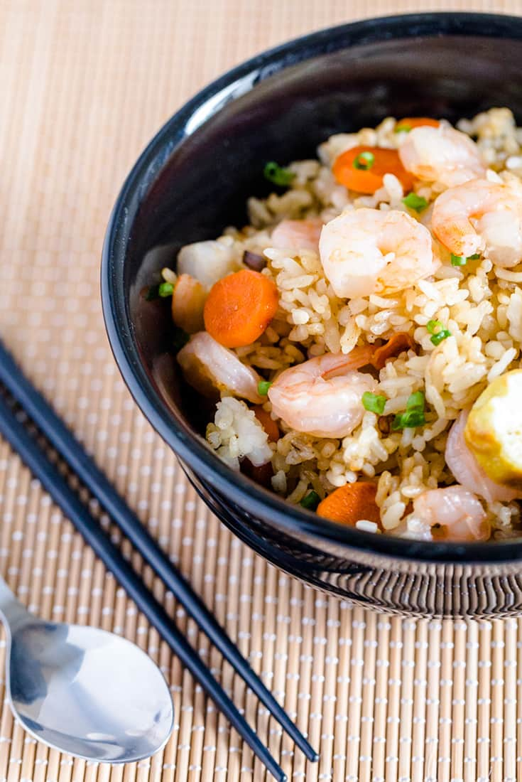 Japanese fried rice with shrimp in a black bowl next to a spoon and chopsticks on a bamboo mat