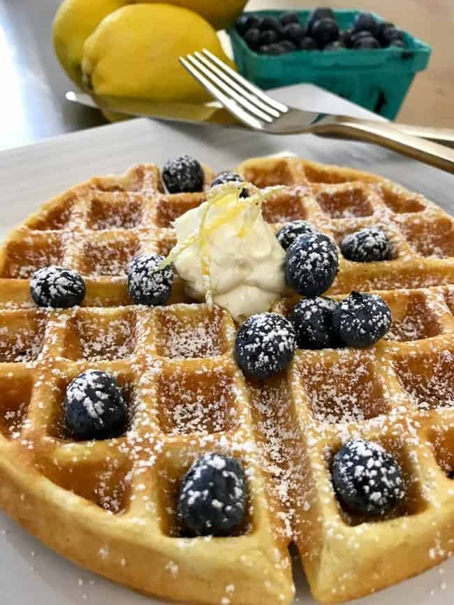 waffle topped with mascarpone and blueberries on a white plate next to a fork and knife with lemons and blueberries in the background