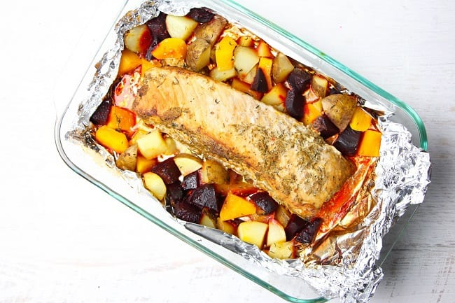 overhead view of roasted garlic and herb pork loin, potatoes, beets and squash in a glass baking dish lined with foil, on a white table
