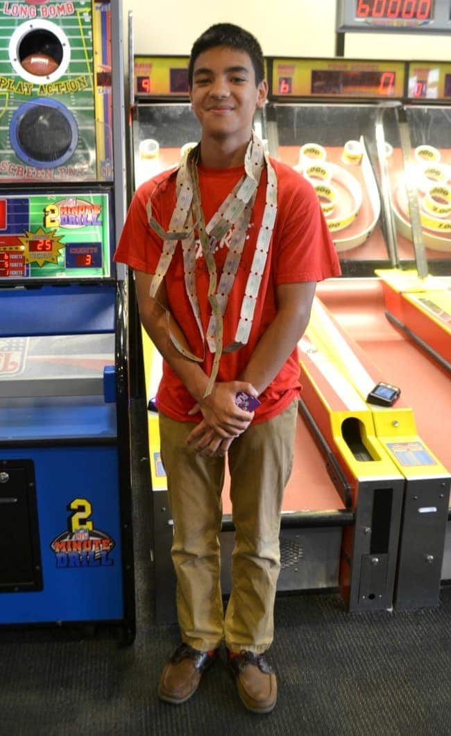 a young man with tickets around his neck standing in front of skee ball machines