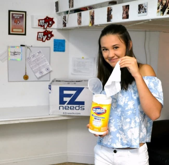 a girl in her dorm holding a container of Clorox wipes with an EZ needs box in the background