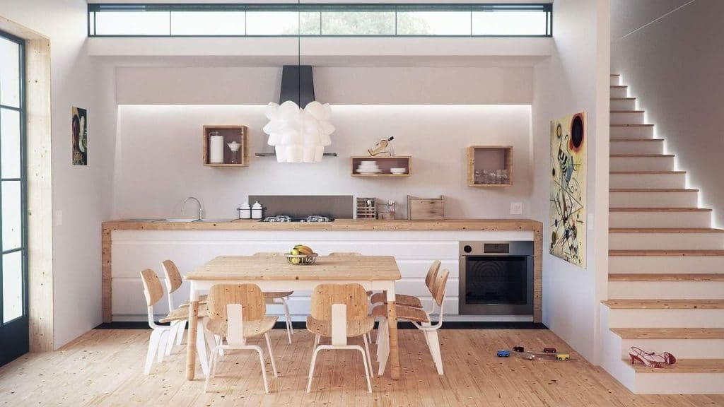 a kitchen with a table and chairs, a counter and an oven, next to stairs