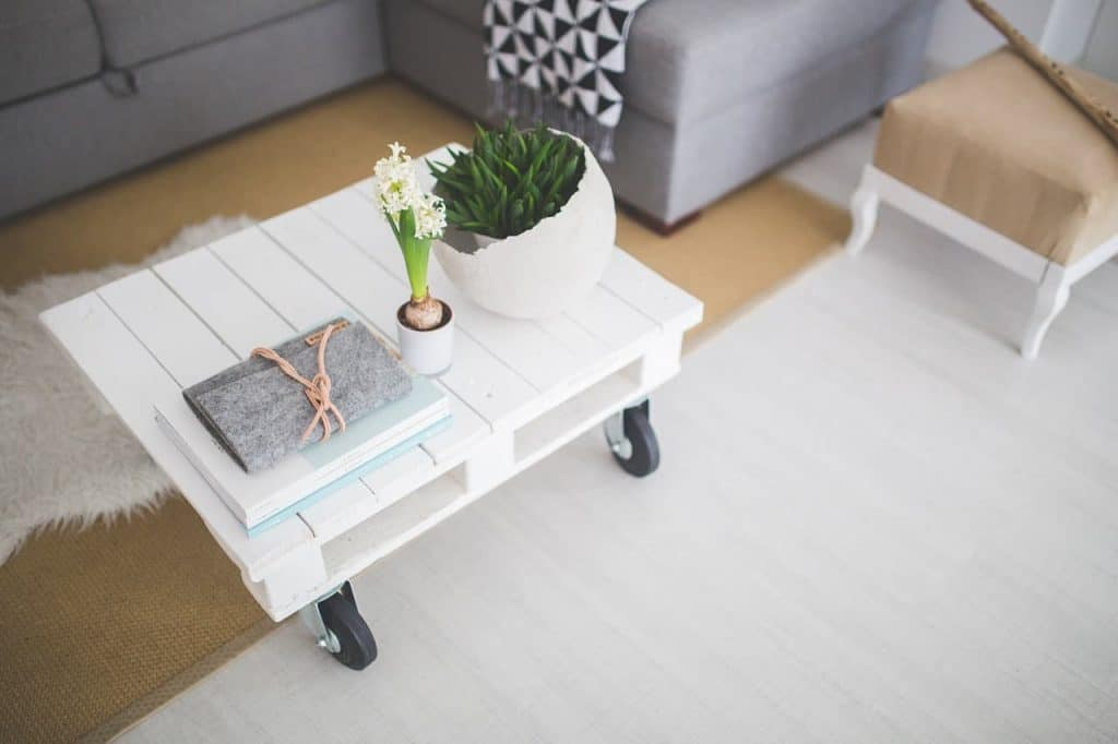 a living room with a white rolling table with books and plants on it, and a couch in the background