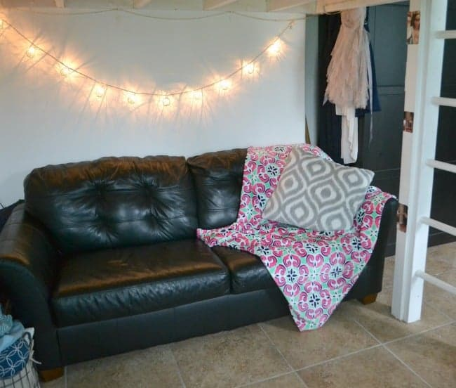 a throw blanket and pillow on a black couch with a string of lights on the wall behind it