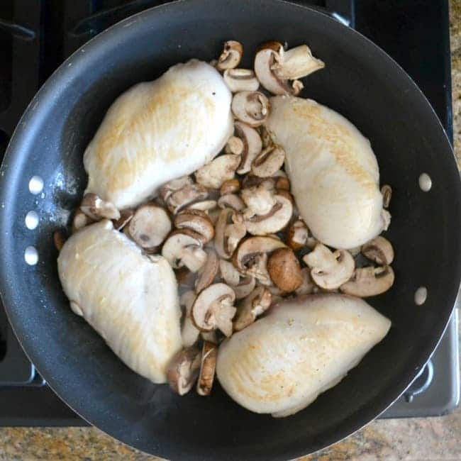 chicken and mushrooms being cooked in olive oil in a pan