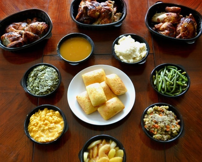 three rotisserie chickens and several side dishes on a brown table