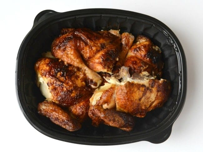 overhead view of cut up rotisserie chicken in a black dish on a white background