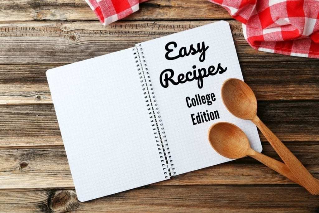 a graph notebook with the words Easy Recipes College Edition on the page with wooden spoons on it, on a wood table next to a red and white checkered cloth
